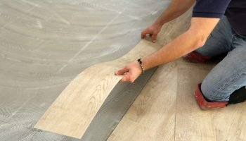 worker installing new vinyl tile floor